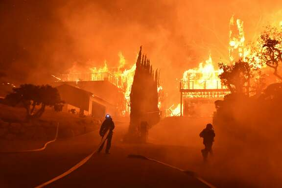 In this photo provided by the Ventura County Fire Department, firefighters work to put out a blaze burning homes early Tuesday, Dec. 5, 2017, in Ventura, Calif. Authorities said the blaze broke out Monday and grew wildly in the hours that followed, consuming vegetation that hasn't burned in decades. (Ryan Cullom/Ventura County Fire Department via AP)