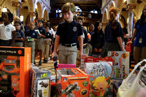 Students from St. Anthony Cathedral Basilica School leave toys on the altar to donate to the Empty Stocking Fund on Tuesday morning. The school's preschool through 8th grade students donate around 200 toys each year.  Photo taken Tuesday 12/5/17 Ryan Pelham/The Enterprise