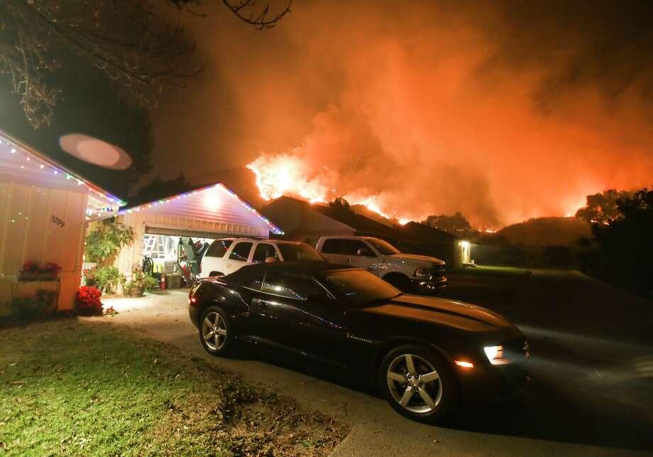 A wildfire burns along a hillside near homes in Santa Paula, California, on December 5, 2017. Photo: RINGO CHIU/AFP/Getty Images