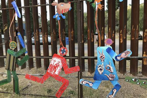 This photo taken Monday, Dec. 4, 2017, shows the international boundary with the United States decorated with colorful public art that protests immigration policies in Nogales Mexico. The figures portray a U.S. Border Patrol officer chasing several migrants. The federal government on Tuesday, Dec. 5, 2017, issued its most complete statistical snapshot of immigration enforcement under President Donald Trump, saying Border Patrol arrests plunged to a 45-year low while arrests by deportation officers soared. (AP Photo/Anita Snow)