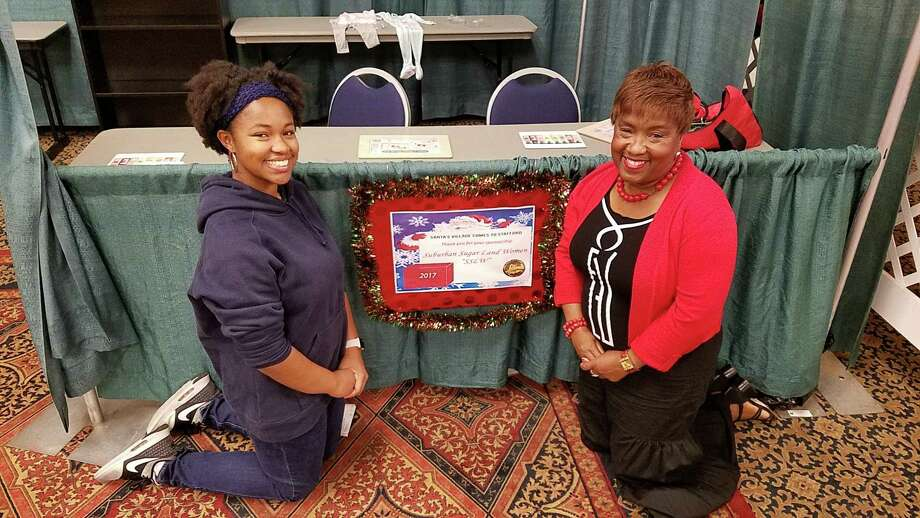 Forche Bridges and Mable Scott Austin take a minute in front of the Suburban Sugar Land Women table recently during a celebration ofSanta Village coming to the Stafford Centre. Photo: Courtesy Photo