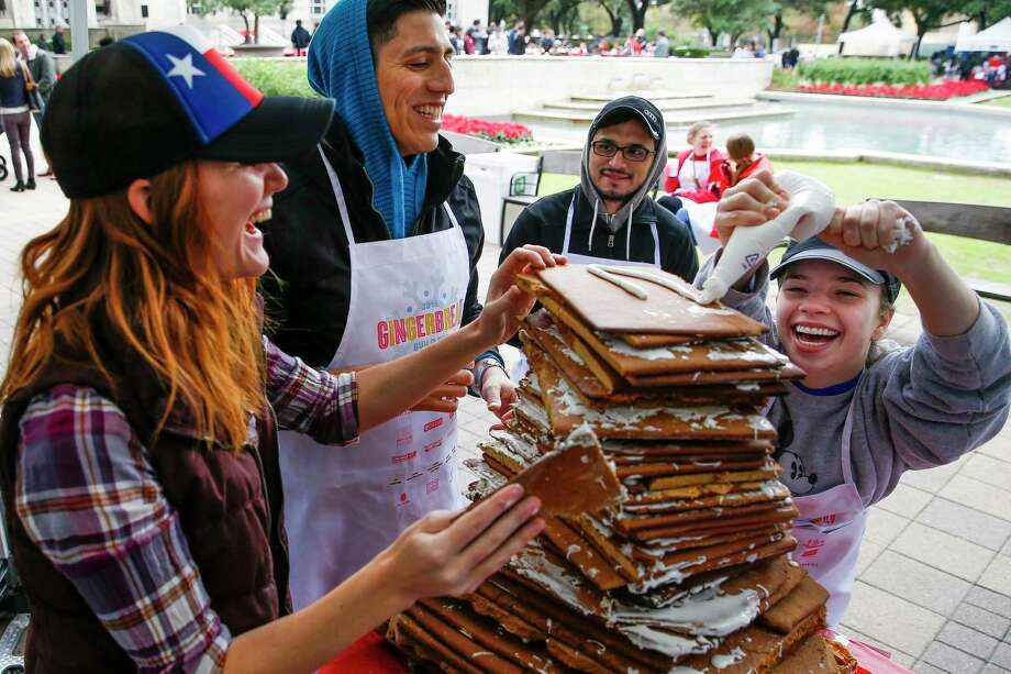 Morris Architects Emily Keller, left, and Irving Gomez, center, laugh as Mary Taylor Carwile, right, struggles to reach to the top of their christmas mountain to put on a layer of frosting as they compete to build the tallest gingerbread creation at the Gingerbread Build Off  Dec. 10, 2016. Photo: Michael Ciaglo / Houston Chronicle, Staff / © 2016  Houston Chronicle