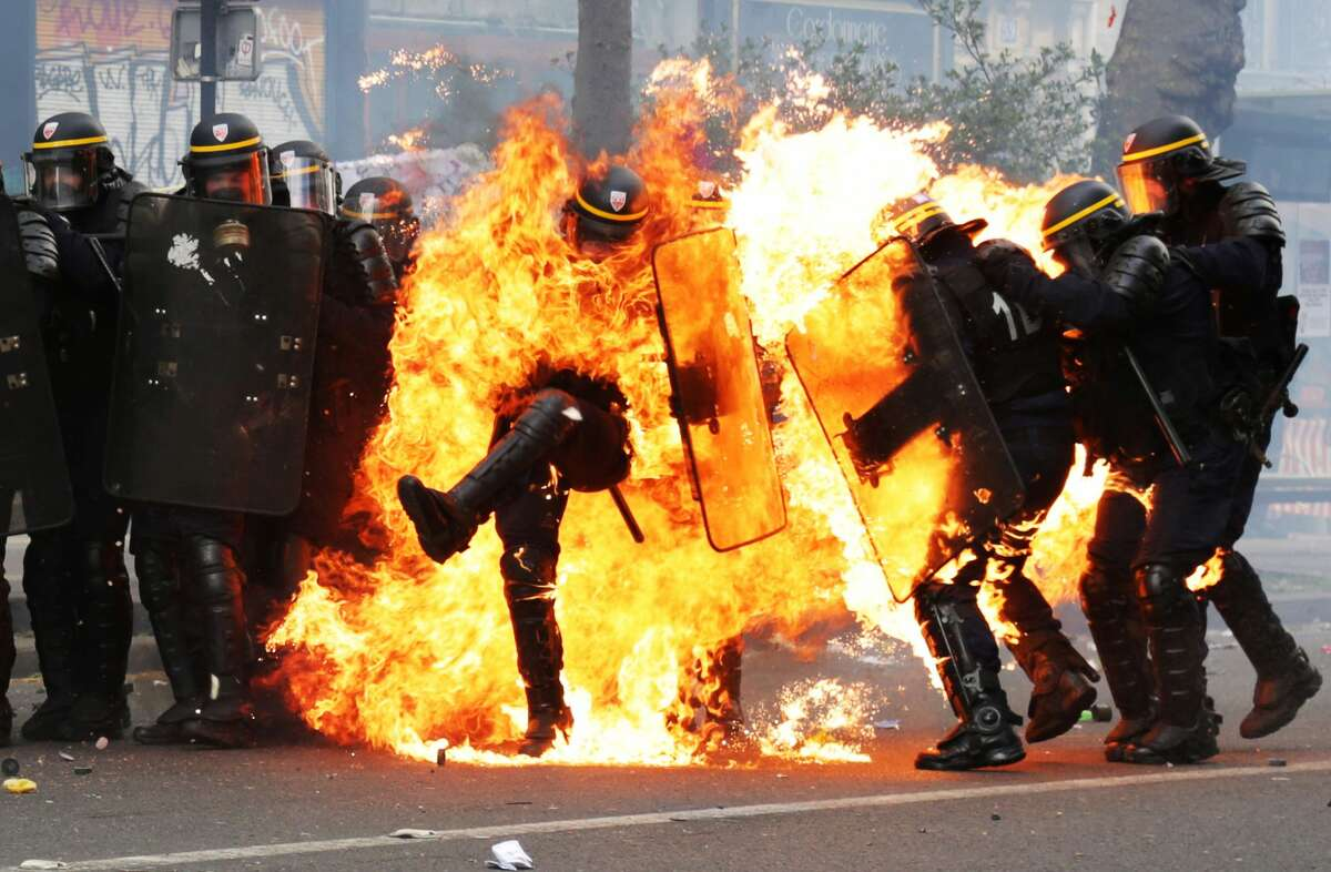 French CRS anti-riot police officers are engulfed in flames as they face protesters during a march for the annual May Day workers' rally in Paris on May 1, 2017. (Photo credit should read ZAKARIA ABDELKAFI/AFP/Getty Images)