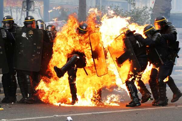 TOPSHOT - French CRS anti-riot police officers are engulfed in flames as they face protesters during a march for the annual May Day workers' rally in Paris on May 1, 2017. / AFP PHOTO / Zakaria ABDELKAFI        (Photo credit should read ZAKARIA ABDELKAFI/AFP/Getty Images)