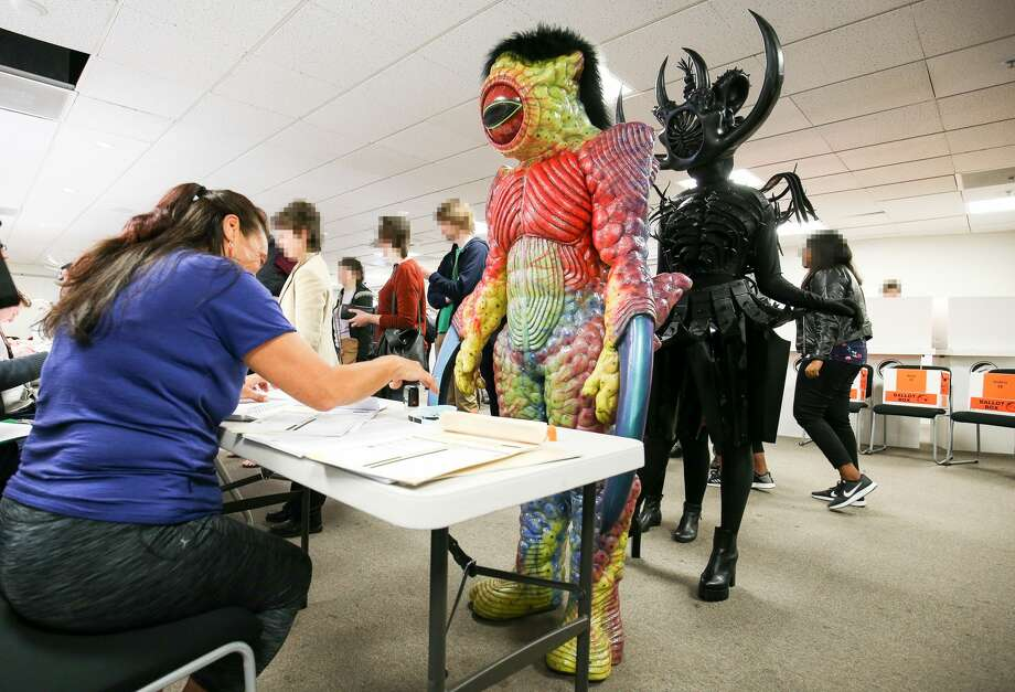 Dylan Nicholson (L) and Tarikura Kapea, dressed in World of WearableArt garments 'Watcher in the Water' by Craig McMillan of New Zealand and 'Cambrian Regeneration' by Ran Xu of China respectively, prepare to vote at Wellington City Library on September 23, 2017 in Wellington, New Zealand. Voters head to the polls today to elect the 52nd Parliament of New Zealand.  (Photo by Hagen Hopkins/Getty Images) Photo: Hagen Hopkins/Getty Images