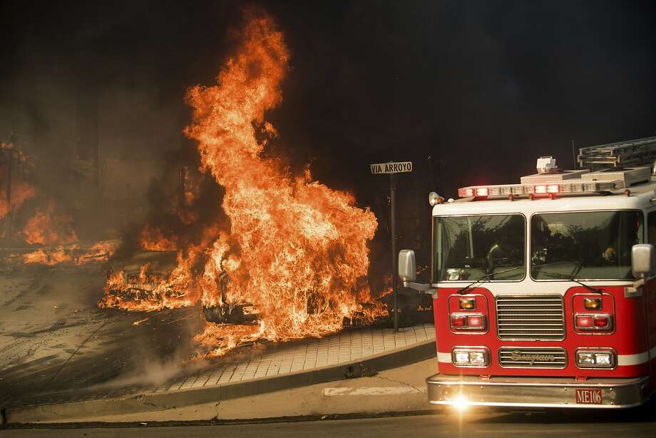 A firetruck passes burning vehicles as a wildfire rages in Ventura on Tuesday. Photo: Noah Berger, Associated Press