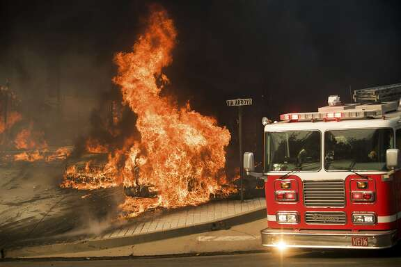 A firetruck passes burning vehicles as a wildfire rages in Ventura, Calif., on Tuesday, Dec. 5, 2017. (AP Photo/Noah Berger)