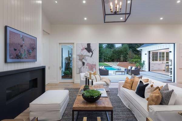 The living room hosts a gas fireplace, vaulted ceiling, and collapsible glass wall that opens to the backyard.