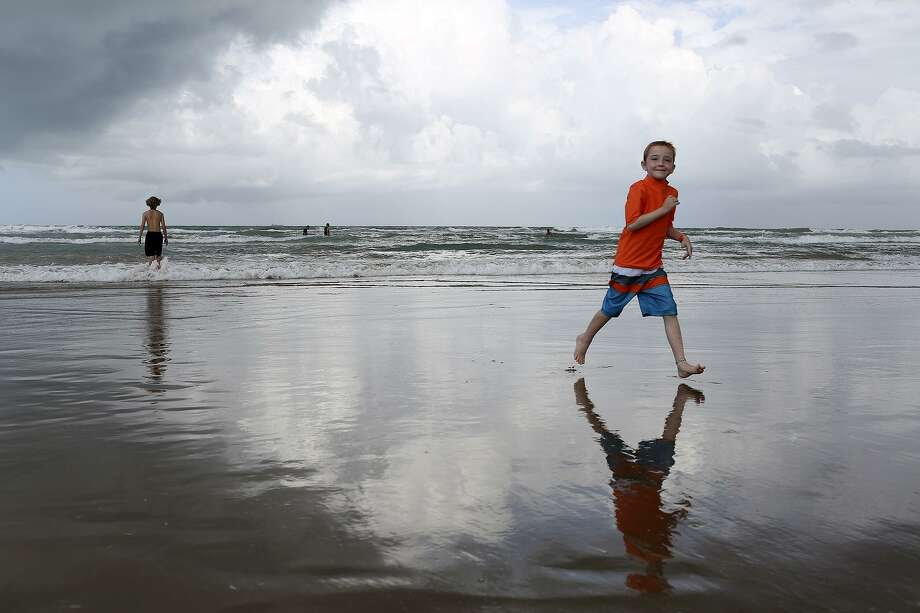 A storm approaches as Rowan plays on the beach with his brother, Ian, 17, at South Padre Island on June 19, 2016. The family trip was part of a bucket list of fun activities before Rowan's translant and hospitilization. On trips to the beach, Rowan writes messages in the sand to his closest friends who have passed; in 2016 the number was seven. Photo: Lisa Krantz / SAN ANTONIO EXPRESS-NEWS / SAN ANTONIO EXPRESS-NEWS