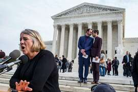 Debbie Munn speaks outside the Supreme Court building as justices heard oral arguments regarding the baker who refused to make a cake for her sonÕs same-sex wedding, in Washington, Dec. 5, 2017.  The conviction of Jack Phillips under Colorado's antidiscrimination law has attracted extraordinary attention; on the steps behind Munn are her son, Charlie Craig, right, and Dave Mullins. (Zach Gibson/The New York Times)