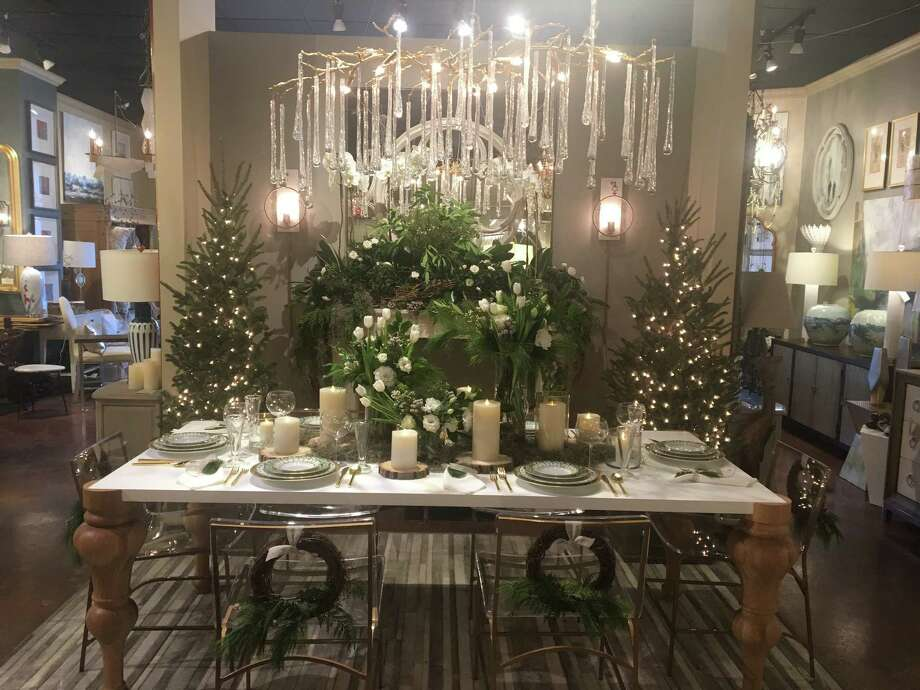 "Connie LeFevre of Design House at the Houston Design Center went for a simple but luxurious display in her tablescape. Her them was ""From Harvey to Hygge,"" following the Scandinavian term for wintry comfort. He hung grapevine wreaths from the back of chairs and used greenery and white flowers in her centerpiece. A stone fireplace is filled with greenery and more white flowers and flanked by two trees with sparkling white lights. Above it all hangs a chandelier dripping with icicle-like crystals. Photo: Diane Cowen / Houston Chronicle"