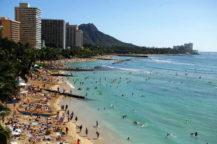 Tourists enjoy sunbathing, surfing, boating and swimming at Waikiki beach in Honolulu, Hawaii, on January 1, 2010. Waikiki, which is a popular tourist destination, was a retreat for Hawaiian royalty in the 1800s. Much like the locals and tourists of today, Hawaiian royalty enjoyed surfing at Waikiki on early forms of longboards. AFP PHOTO/Jewel SAMAD (Photo credit should read JEWEL SAMAD/AFP/Getty Images)