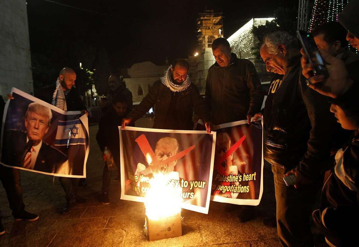 Palestinian protesters burn pictures of US president Donald Trump at the manger square in Bethlehem on December 5, 2017. US President Donald Trump told Palestinian leader Mahmud Abbas in a phone call that he intends to move the US embassy from Tel Aviv to Jerusalem, Abbas's office said. / AFP PHOTO / Musa AL SHAERMUSA AL SHAER/AFP/Getty Images