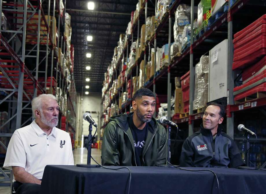 Retired Spurs superstar Tim Duncan, flanked by San Antonio Food Bank CEO Eric S. Cooper, right, and Spurs Coach Gregg Popovich, on Tuesday announced a matching challenge in which he will donate up to $500,000 to help feed hungry families this holiday season. For each $1 donated to the food bank, Duncan will contribute $2 until the half-million-dollar mark is reached. Photo: Ron Cortes /For The San Antonio Express-News