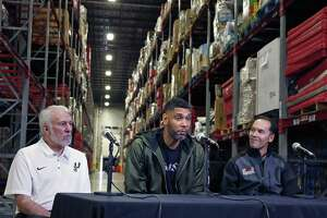 Retired Spurs superstar Tim Duncan, flanked by San Antonio Food Bank CEO Eric S. Cooper, right, and Spurs Coach Gregg Popovich, on Tuesday announced a matching challenge in which he will donate up to $500,000 to help feed hungry families this holiday season. For each $1 donated to the food bank, Duncan will contribute $2 until the half-million-dollar mark is reached.