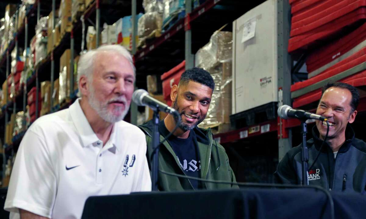 In pre-pandemic days, San Antoino Food Bank CEO Eric Cooper (right) laughs and Tim Duncan (center) smiles as Spurs Coach Gregg Popovich jokes with reporters in the warehouse of the San Antonio Food Bank in December 2017. The Spurs organization - and Duncan and Popovich personally - are longtime supporters of the Food Bank, including during the novel coronavirus crisis.