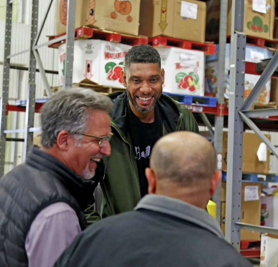 After a Tuesday news conference where he announced a major matching gift to the San Antonio Food Bank, retired Spur Tim Duncan chats with Miguel Guerra, left, and Richard Plume, two men who accompanied Duncan to the U.S. Virgin Islands to do recovery work after a massive hurricane hit. Photo: Ron Cortes /For The San Antonio Express-News