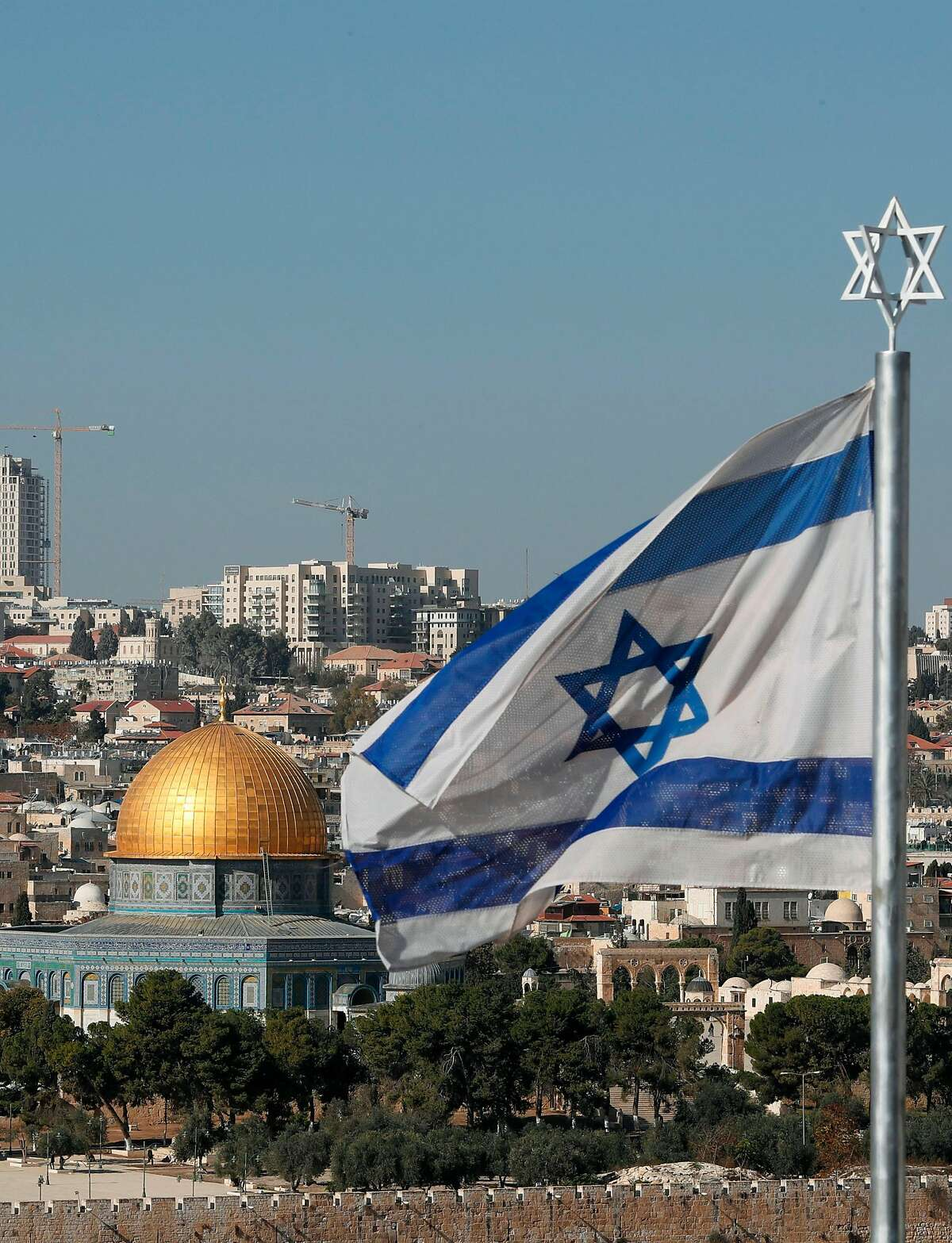 The Israeli flag flutters in front of the Dome of the Rock mosque and th city of Jerusalem, on December 1, 2017. Two Israeli cabinet ministers said on November 30 that they hoped US President Donald Trump was about to move his country's embassy from Tel Aviv to Jerusalem, as a decision deadline neared. The issue is deeply controversial. Shifting the building could be seen as a de facto recognition of Israel's claim over the whole city, including predominantly Palestinian east Jerusalem. / AFP PHOTO / THOMAS COEXTHOMAS COEX/AFP/Getty Images
