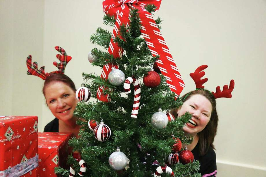 Sisters Lucy Toler and Laurie Dugdale were caught playing behind the Trinity Valley Refuge Christmas tree on Saturday night at the Country Christmas celebration at the Dayton Community Center last Saturday night. Photo: David Taylor