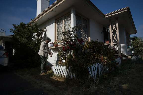 Dorothy DeBose, 77, removes leaves from a pot from her window sill on Thursday, July 27, 2017 in Oakland, CA.