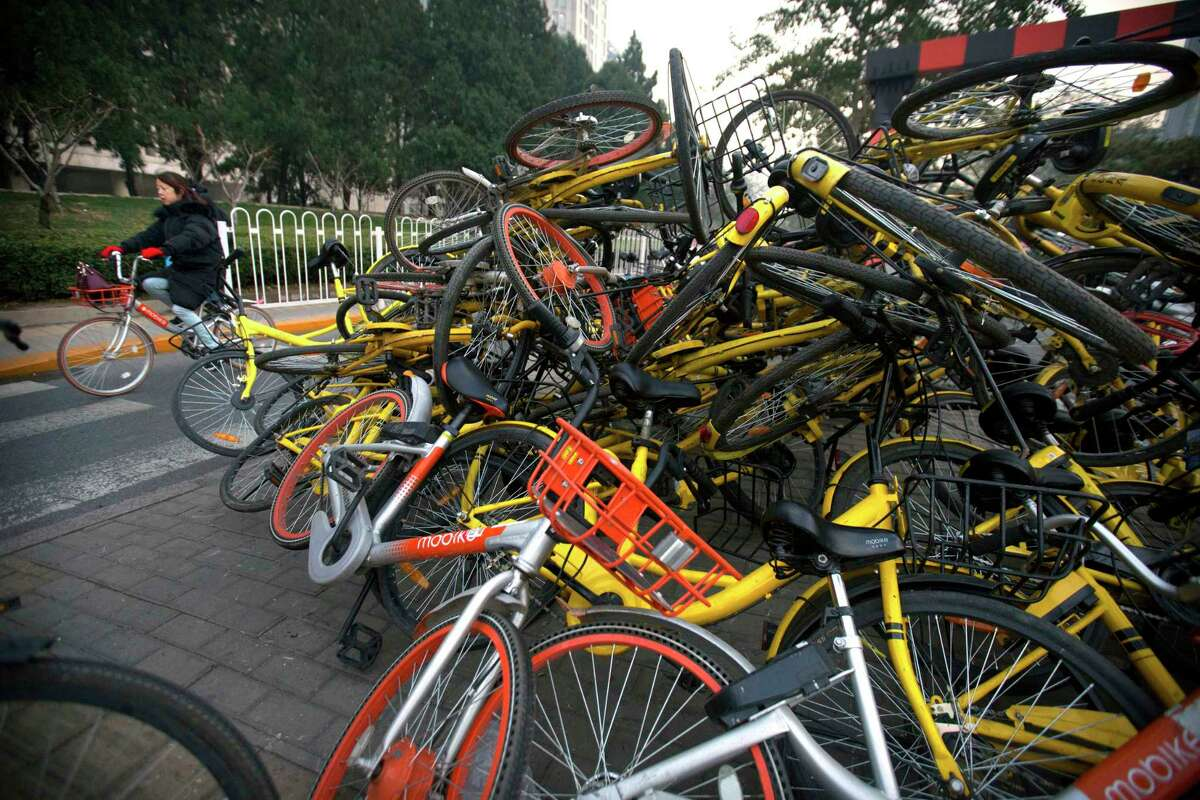 A woman rides a bicycle past Mobike and Ofo branded shared bicycles piled on a traffic median in Beijing on Nov. 21. Chinese government officials have introduced regulations in recent months to help tame China's booming bicycle-sharing industry that has flooded the streets of its major cities with bicycles for hire.