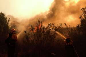 Firefighters try to prevent a portion of The Creek Fire from jumping the 210 freeway in Sylmar on December 5, 2017.