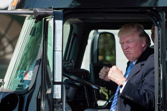US President Donald Trump sits in the drivers seat of a semi-truck as he welcomes truckers and CEOs to the White House in Washington, DC, March 23, 2017, to discuss healthcare. / AFP PHOTO / JIM WATSONJIM WATSON/AFP/Getty Images