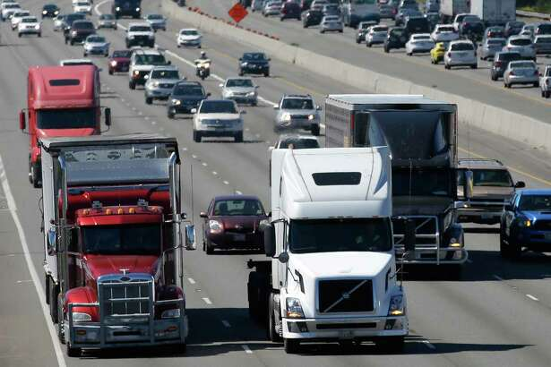 FILE - In this Wednesday, Aug. 24, 2016, file photo, truck and automobile traffic mix on Interstate 5, headed north through Fife, Wash., near the Port of Tacoma. Truckers are warning that a government plan to electronically limit the speed of tractor-trailer rigs will lead to highway traffic jams and even an increase in deadly run-ins with cars allowed to travel at faster speeds. (AP Photo/Ted S. Warren, File)