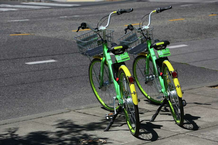 LimeBike, one of a handful of dockless bike companies interesting in distributing bikes around Houston, like these two in Seatlle's lower Queen Anne neighborhood on July 26, 2017. Bikes are unlocked via an app and do not come with helmets. Photo: GENNA MARTIN, SEATTLEPI.COM / SEATTLEPI.COM