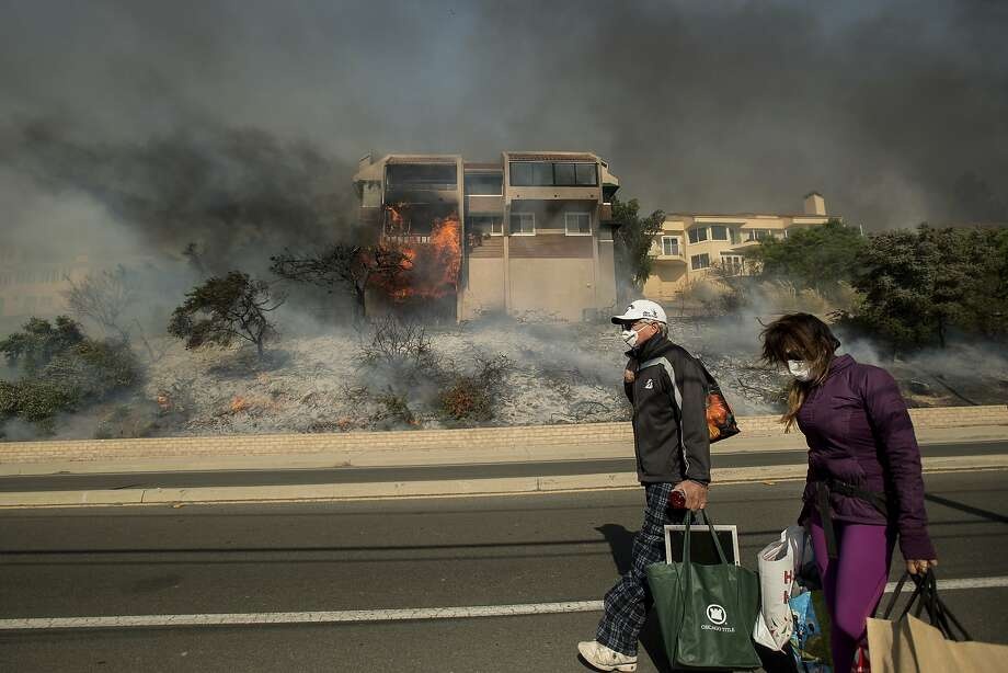 James and Josie Ralstin carry belongings from their Ventura, Calif., home as flames from a wildfire consume another residence on Tuesday, Dec. 5, 2017. The couple evacuated early Tuesday morning as the fire approached, but returned to retrieve medications and other property. (AP Photo/Noah Berger) Photo: Noah Berger, Associated Press