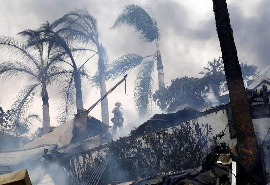 A firefighter stands under windswept palm trees as he hoses down smoldering debris in Ventura, Calif., Tuesday, Dec. 5, 2017. Ferocious Santa Ana winds raking Southern California whipped explosive wildfires Tuesday, prompting evacuation orders for thousands of homes. Photo: Daniel Dreifuss, Associated Press