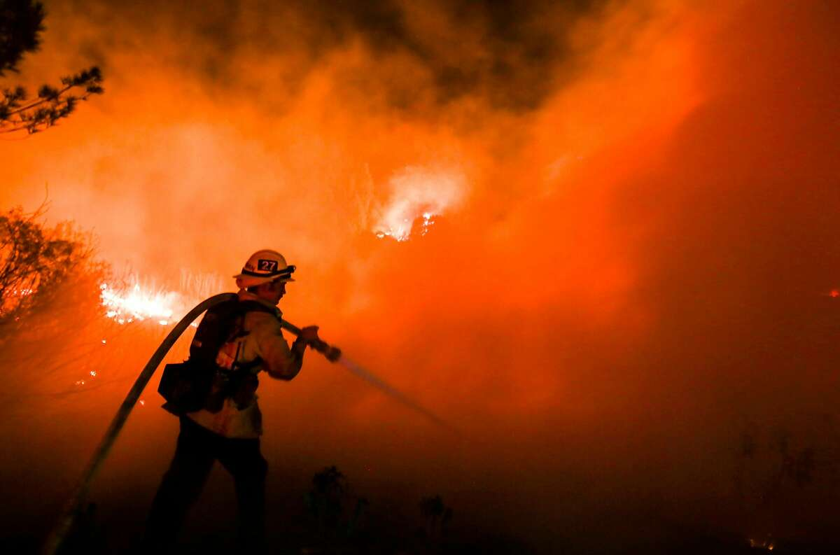 A firefighter battles a wildfire as it burns along a hillside near homes in Santa Paula, California, on December 5, 2017. Fast-moving, wind-fueled brush fire exploded to about 10,000 acres in Ventura County Monday night, forcing hundreds of people to flee their homes, officials said. / AFP PHOTO / RINGO CHIURINGO CHIU/AFP/Getty Images