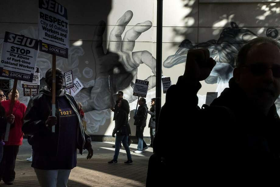 Striking Oakland city workers picket at Frank Ogawa Plaza in the city's downtown. Photo: Paul Kuroda, Special To The Chronicle