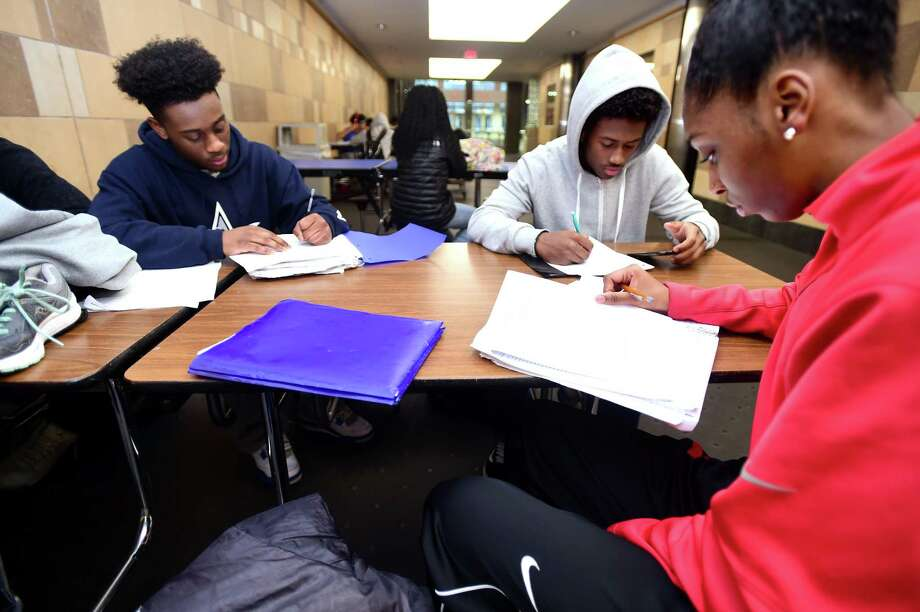 From left, Naszier Robinson, Neal Eley and Shayna Smith of the James Hillhouse High School indoor track team do homework after school at the Floyd Little Athletic Center Tuesday. Photo: Arnold Gold / Hearst Connecticut Media / New Haven Register