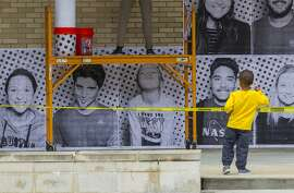 Jaxon Ajoku, 3, whose mother is the director of the Center for Diversity and Inclusion at the University of Houston, plays in front of the posters being pasted on a wall outside the student center of people that were just photographed by the Inside Out Project's mobile photo booth truck at the University of Houston, Tuesday, Dec. 5, 2017, in Houston. The exhibit is intended to urge Congress to pass the DREAM act before the end of the year. ( Mark Mulligan / Houston Chronicle )