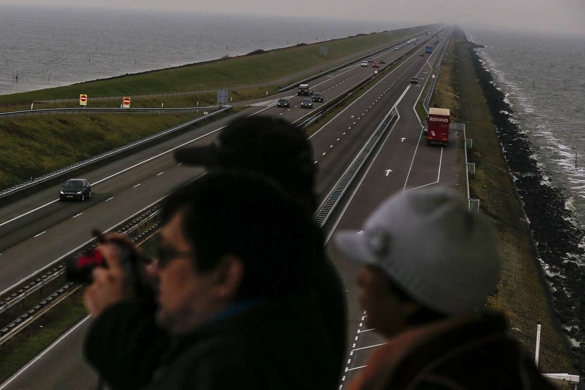 People take photos of the Afsluitdijk, a 20-mile dam constructed after a flood in 1916, as it stretches off into the horizon in Den Oever, the Netherlands.