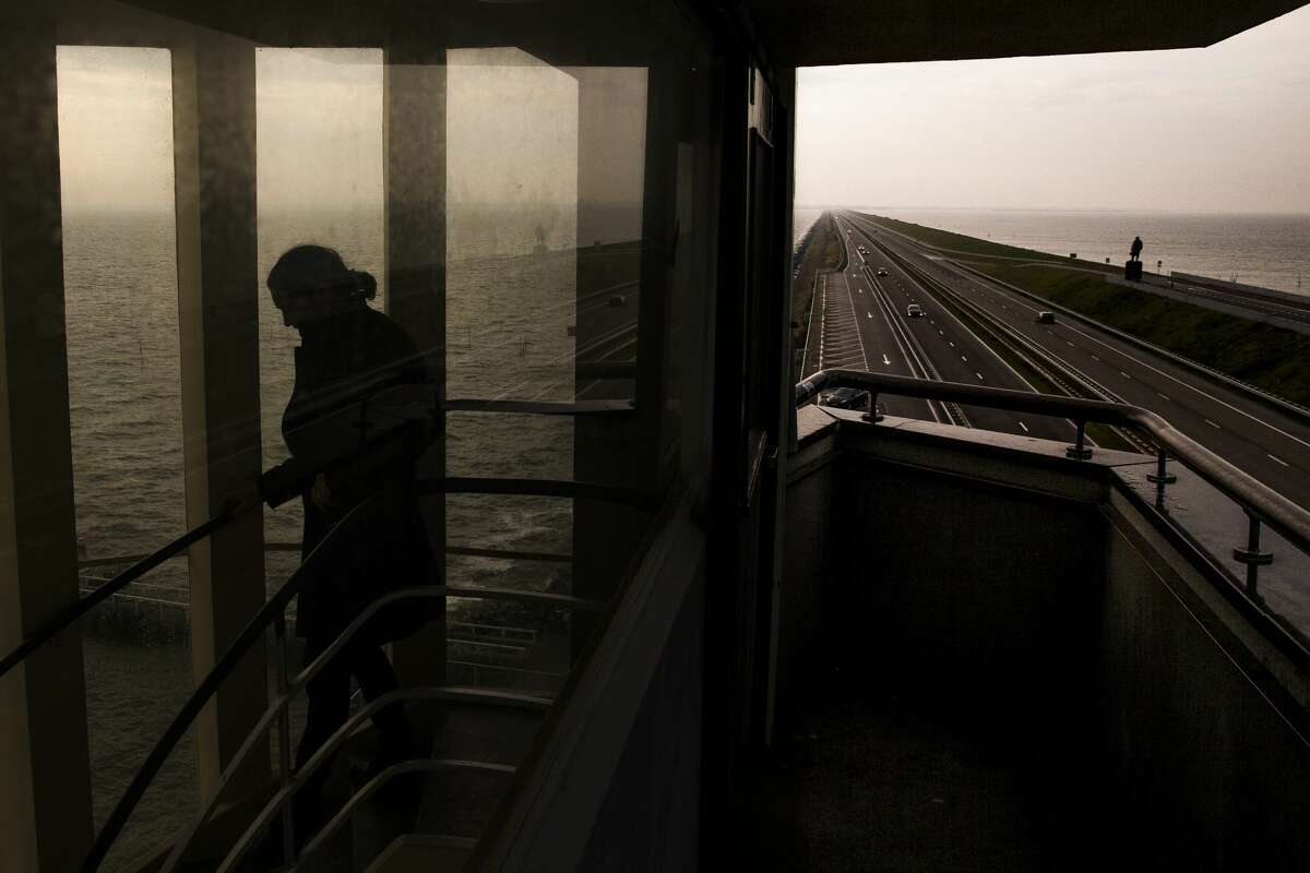 A man walks down the staircase of the Vlieter Monument overlooking the Afsluitdijk, a 20-mile dam constructed after a flood in 1916, as it stretches off into the horizon in Den Oever, the Netherlands.
