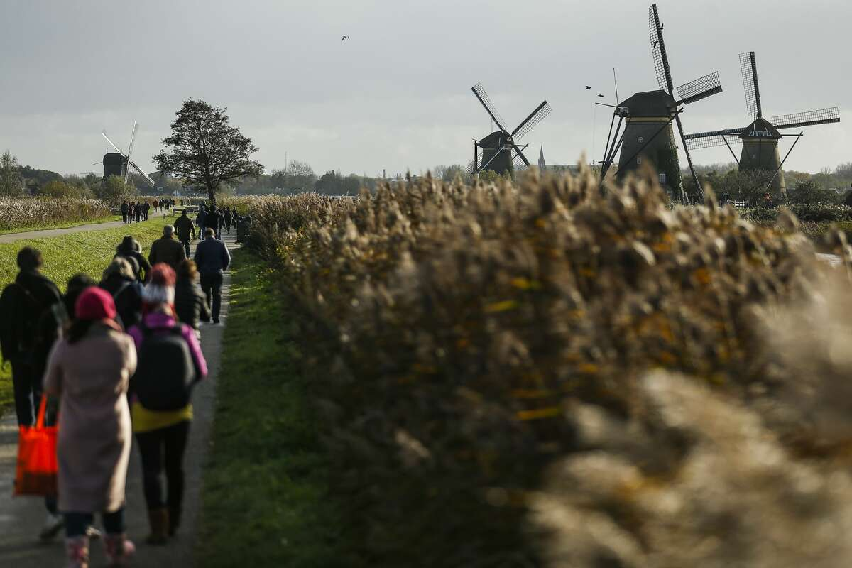 Tourists walk past the windmills at Kinderdijk. The windmills, which are now a UNESCO World Heritage Site,were built around 1740to pump water out of the area that sits below sea level.