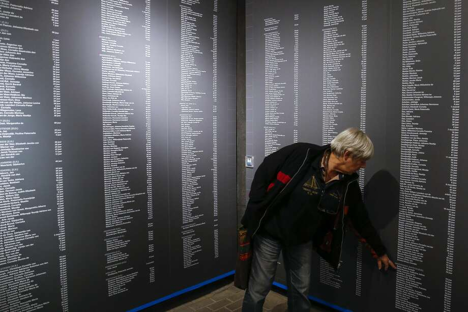Ria Geluk, who was 6 during the 1953 flood that claimed the lives of 1836 people in the Netherlands, points out the names of her grandparents who were killed in the flood at a memorial at the Watersnoodmuseum in Ouwerkerk. Photo: Michael Ciaglo