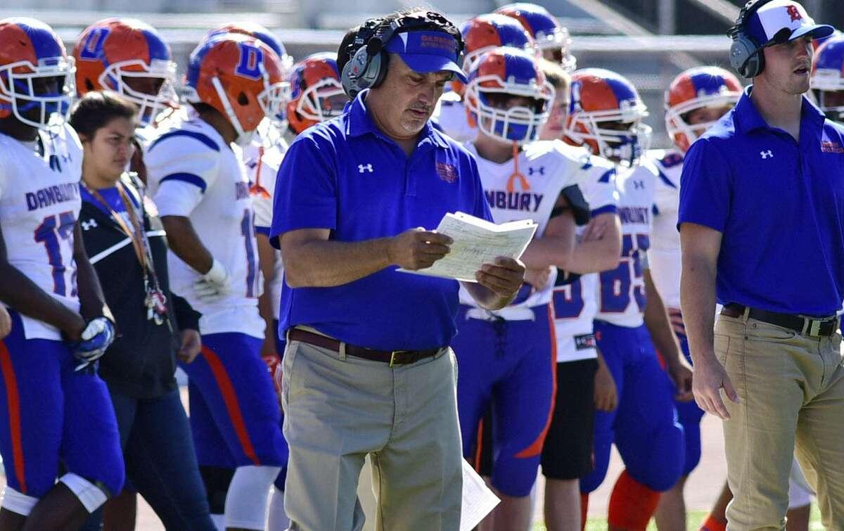 Danbury High School football head coach Alex Trasacco consults the game plan as Harding High School takes on Danbury during their FCIAC football game at Kennedy Stadium in Bridgeport, Conn. Saturday, September 24, 2016.