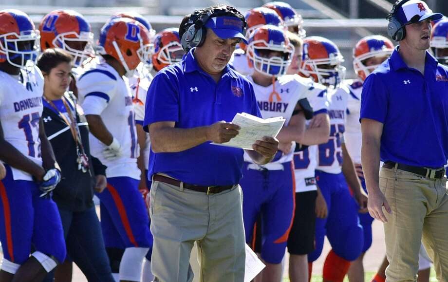 Danbury High School football head coach Alex Trasacco consults the game plan as Harding High School takes on Danbury during their FCIAC football game at Kennedy Stadium in Bridgeport, Conn. Saturday, September 24, 2016. Photo: Erik Trautmann / Hearst Connecticut Media / Norwalk Hour