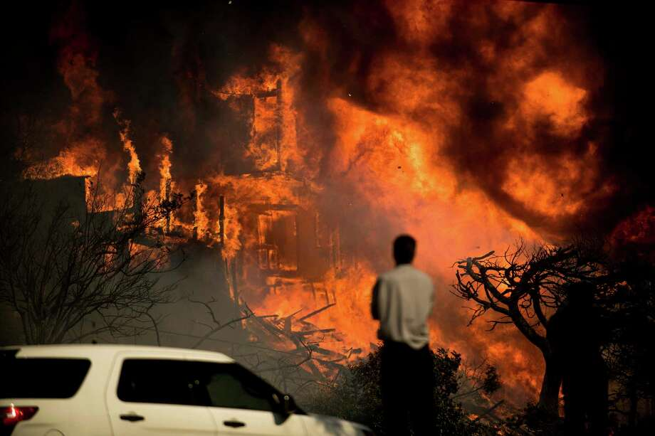 A man watches flames consume a residence as a wildfire rages in Ventura, Calif., Tuesday, Dec. 5, 2017. Ferocious winds in Southern California have whipped up explosive wildfires, burning a psychiatric hospital and scores of other structures. (AP Photo/Noah Berger) Photo: Noah Berger, FRE / Noah Berger