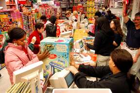 KING OF PRUSSIA, PA - NOVEMBER 28:  Customers pay for their items while doing their Black Friday shopping at KB Toys, which opened at 5am, in the King of Prussia Mall November 28, 2003 in King of Prussia, Pennsylvania.  Black Friday is traditionally when stores get out of the red and start making a profit for the year. Economists expect a 5 percent increase in holiday sales over last year.  (Photo by William Thomas Cain/Getty Images)