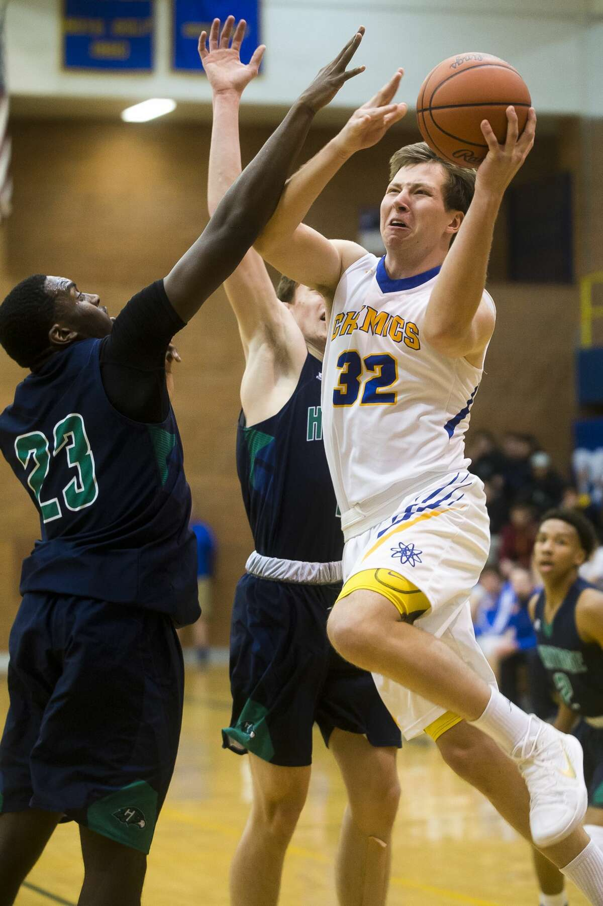 Midland senior Garrett Willis takes a shot as Saginaw Heritage senior Justin McMurren guards him during their game on Tuesday, Dec. 5, 2017 at Midland High School. (Katy Kildee/kkildee@mdn.net)