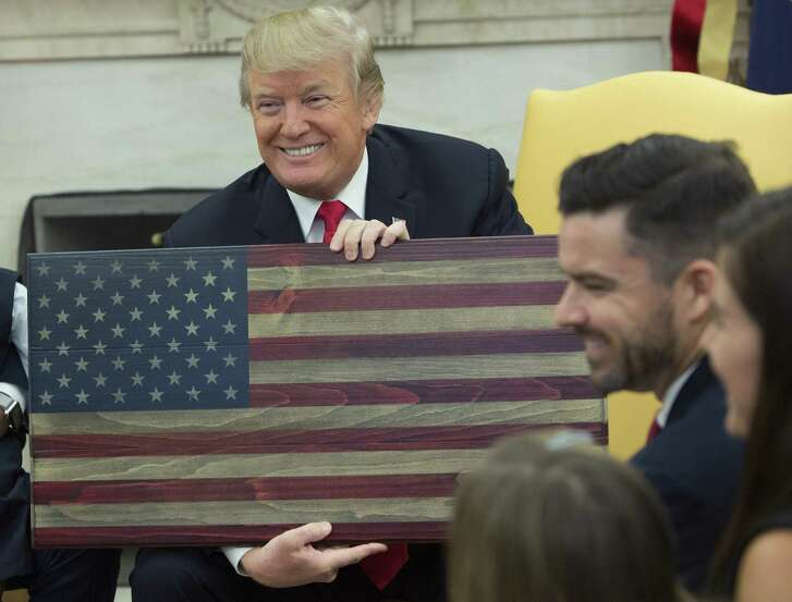 President Donald Trump holds an American flag plaque made by Brian Steorts, owner of Flags of Valor, during a meeting in the Oval Office Tuesday. Trump hosted four families from around the country to hear how tax reform could grow their businesses.(Bloomberg)