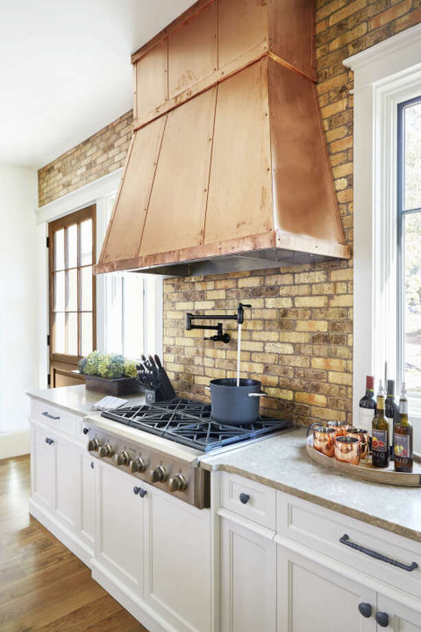 3) Heavy Up the Metal The open shelving trend isn't going anywhere and in a kitchen void of upper cabinetry, the hood is inevitably the centerpiece. Dress it accordingly! Copper sheeting, with coordinating straps and rivets, adds age-old warmth. See more at copperhoods.com  Photo: Photographer: Jean Allsopp, Designer: Joanna Goodman For Christopher Architecture & Interiors
