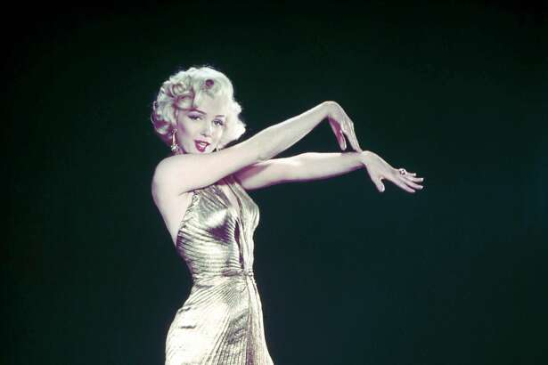 Actress Marilyn Monroe posing wearing her famous gold lame gown designed by Bill Travilla for a publicity still for the motion picture Gentlemen Prefer Blondes.  (Photo by Ed Clark/The LIFE Picture Collection/Getty Images)