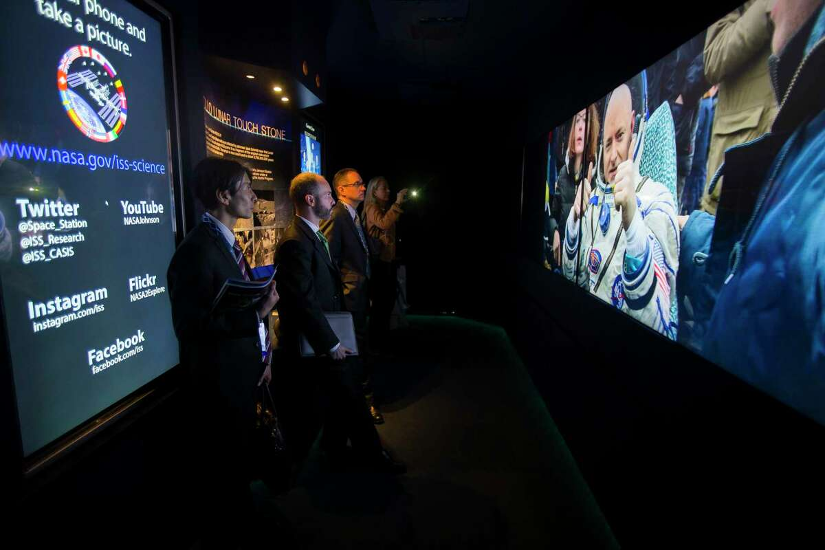 Visitors to one of NASA's exhibits at SpaceCom watch a video inside a trailer at the George R. Brown Convention Center, Tuesday, Dec. 5, 2017, in Houston. ( Mark Mulligan / Houston Chronicle )