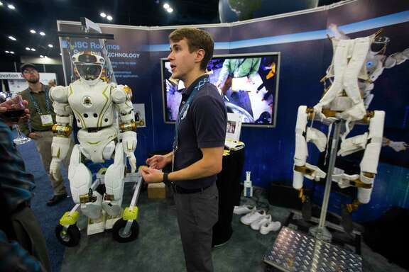 Stu Donnan, who works at NASA's Johnson Space Center, talks about the Valkyrie bipedal humanoid robot on display on SpaceCom's exhibit floor during an opening reception at the George R. Brown Convention Center, Tuesday, Dec. 5, 2017, in Houston. ( Mark Mulligan / Houston Chronicle )