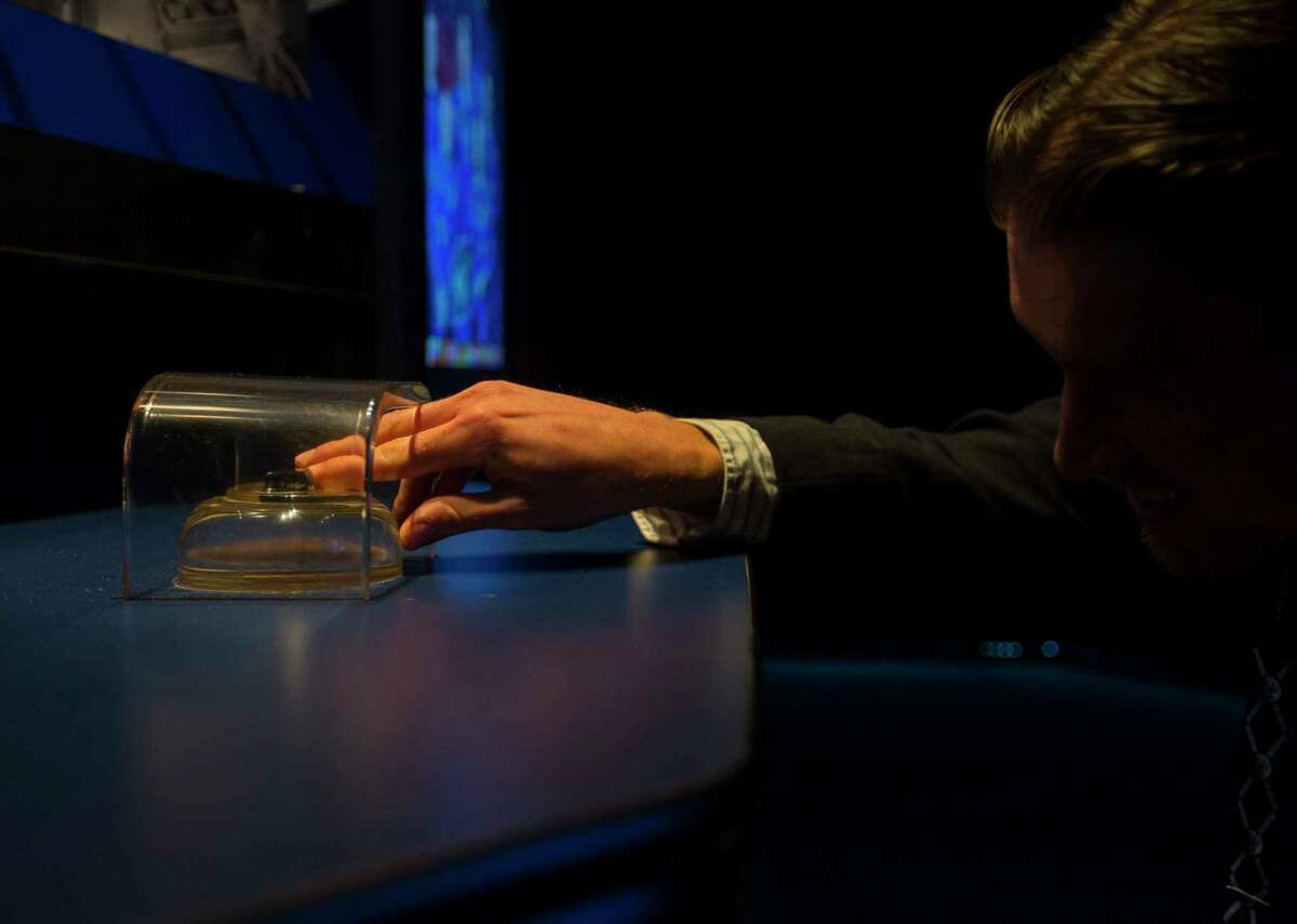 Nicholas Campbell touches a piece of rock that was collected on the moon during the Apollo 17 mission during an opening reception at the George R. Brown Convention Center, Tuesday, Dec. 5, 2017, in Houston. ( Mark Mulligan / Houston Chronicle )